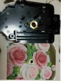 掛け時計の修理について。 お気に入りの掛け時計が、何度電池を入れ換えても、すぐに止まってしまうので、ムーブメントを購入して自分で変えようと思います。   (画像)真ん中にナットのようなものがはまっていて、黒いムーブメントを引っ張っても、テコの原理で持ち上げても外れません(-_-;)  薔薇の方が表側ですが、裏のムーブメントを回すと真ん中のゴールドの部分が一緒に回ります。 ゴールドの部分を固定...