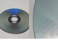 ディスク記録面が白く曇ったりするのは何故でしょうか? (※画像あり)  中古で購入した複数のCDやDVDの記録面に、白く曇ったような跡 (以下、白もや)があります(※画像左参照)。 このパターンが一番多く見られるのですが、数珠のような曲線模様 (以下、数珠)が付いているときもあります(※画像右参照)。  白もやは、画像1のように外周側にリング状のときもあれば、 外周側+内周側...