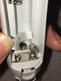 質問です! 電池を取り外したら、写真のように乾電池を入れるところのバネが取れてしまいました。自力で直そうとしてもなかなか、出っ張りに引っ掛けることができません。 この出っ張りみたいな部分にバネを置いた形にして電池を差し込めんでボタンを押せば何とか操作はするのですが、やはり手間がかかりますし、心配です。  またこの出っ張りにくっつける方法はないのでしょうか。教えてください。