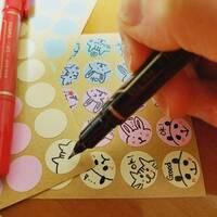 丸シールにイラストを描きたいです!オススメのペンを教えてください!  添付画像のようにイラストや文字を描きたいのですか、マッキーでは上手く書けませんでした(^^; また、当たり前ですが 水性ペンではこす...