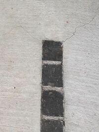 外構 土間コンのひび割れについて。 新築建売のカーポート(コンクリート床部分)が、煉瓦の四隅からひび割れし、ジワジワと広がっています。(入居後もうすぐ1年) 入居後2年までは無料で補修してくれると契約書には書いてあるのですが、ひび割れの部分だけ補修剤を入れると逆に線が目立って汚くなってしまうのかなと思っています。 この程度のひび割れだと放置しかないのでしょうか。上から全体的に薄くコンクリート...