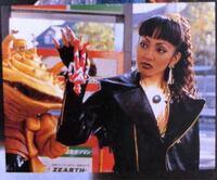 この画像はウルトラマンゼアス2のワンシーンらしいのですが、これは一体どういった状況なのでしょうか? この女性は、ウルトラマンゼアスの人形をプレゼントされているんですか?横の怪獣は悪者で、この女性はウ...