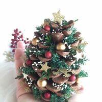 松ぼっくりツリーの材料について 今年画像のような、松ぼっくりを利用した小さなクリスマスツリーをよく見かけて気になっています。 この緑色の葉っぱ?みたいなものはなんという植物ですか? こういった材料などはどこで揃えられるのでしょうか?