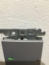 電気スイッチの件で質問させてください。  壁に止めてあったネジが石膏ボードが崩れてきたのか、ネジが外れる状態になってしまい(写真中央部分の下側の穴)、右側の穴にネジで止め直しました。 この止め方でも問...