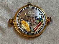 HIROBというお店で時計を購入しました。ただ、中身が他のカルティエの機械とは違いました。画像が荒く見えづらかったらすみません)ただ、年代によって使う機械が変わるので100%のことは言えませ ん。それから、裏蓋にある八角形の中の鳥の刻印が薄いのです。  HIROBさんは偽物を取り扱っているのでしょうか。画像をみて、偽物か判断できる方いらっしゃいますか?