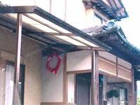 北九州の行橋、田川周辺で民間の玄関先や表から見える壁にフラフープにピラピラが付いた輪っかを掛けている家がたまに目に付くのですが これは何かわかる方いらっしゃいますか?  この写真では赤色の輪ですが、紫...