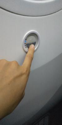 飛行機の窓側の席にあるこのボタンはなんですか? 国内線、ANAの便、窓の下にありました。 青色のランプが、上を押すと上に、下を押すと下に移動しました。