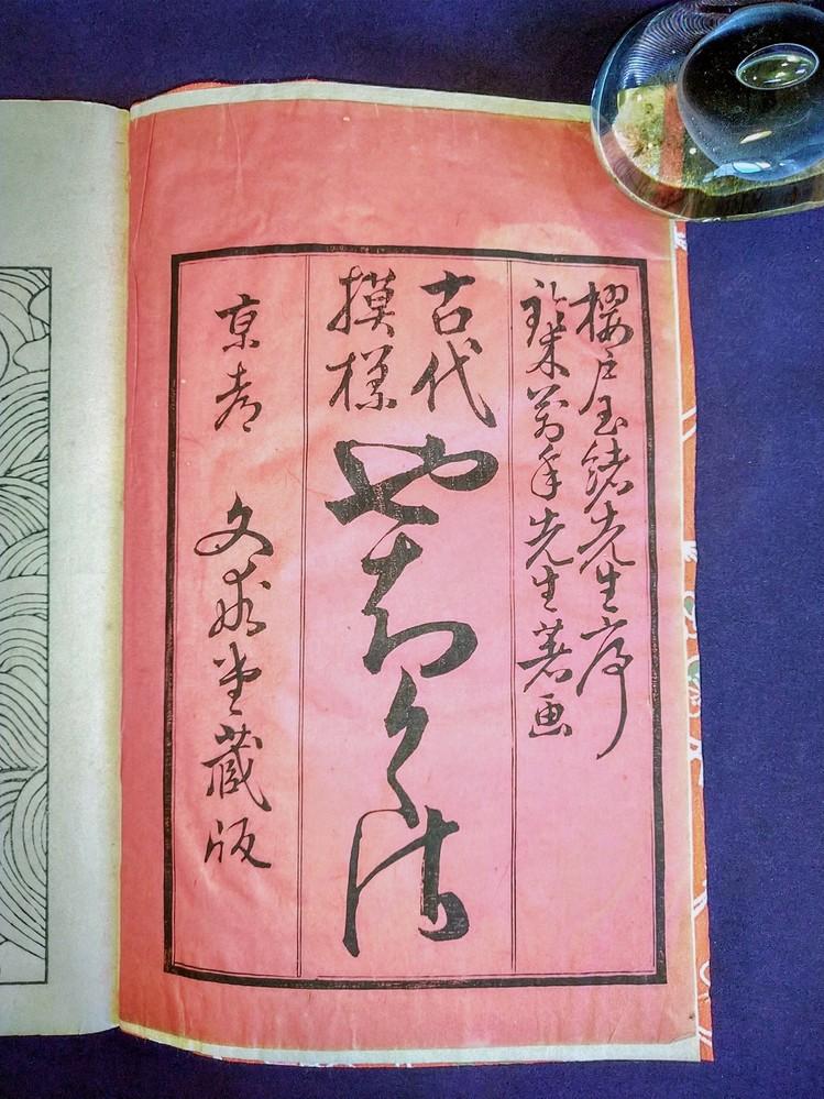 写真の文字の読み方について、何が書いてありますか、お教えください。 「古代模様」の手本帳のような冊子の表題部分であります。 どうぞよろしくお願いします。