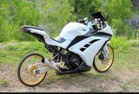 バイクのカスタムについて質問です。 海外の一部地域ではこのようにフルカウルのバイクに自転車のような細いタイヤをつけるカスタムがあるようですが、何故なのでしょうか。 アンバランスでお世辞にもかっこいい...