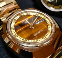 タイガーアイが文字盤の腕時計についての質問です。 文字盤がタイガーアイになっている時計は 「タイガーアイ風」なんでしょうか? 疑問に思った理由は デイト表示の為の窓が開いている時計を見たからです。 石をわざわざくり抜いて 窓を作って文字盤にする事が果たしてできるのかな? と思いました。  どうでしょうか? よろしくお願いいたします。