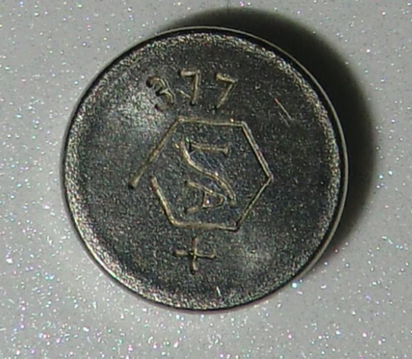 時計の電池で見たことがないものが出てきたので、わかる方はお願いします。 昔のボタン電池で今の対応型番が何かを知りたいです。 画像の電池です。 377と書いてあります。真ん中には六角形があり、六...