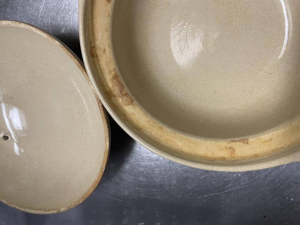土鍋について質問です。 一人暮らしを始めるために亡くなった祖母の家から土鍋を持ってきました。 持ってきたはいいのですが写真のような汚れが縁についていて気になって使う気になれず、キッチン泡ハイターをかけてみたのですが落ちません。 この汚れは焦げの汚れなのでしょうか?それともなにか菌なのでしょうか? また、この汚れの落とし方も教えていただきたいです。 よろしくお願いします。