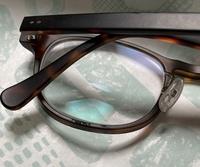 メガネフレームの劣化?  メガネフレームが頬に当たるからでしょうか? 写真のように、メガネの下の部分、 ボコボコとコーティングが浮き上がっているように見えます。 化粧品とかが原因でしょうか? これはだんだん剥がれてきてしまうのでしょうか? 毎朝拭いているのですが、 最近見つけて、なんか文字があったっけ?程度でしたが、今日見たらボコボコが増えているので、何が原因だと思われますか?