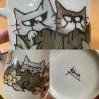 探しています。 猫の手描き絵が書いてあるマグカップの作り主を探しています。(写真参考)  頂いたマグカップを割ってしまいました。とてもお気に入りで、自分でも購入したいと思い、色々と検索をかけましたが、見つかりませんでした。  製作者らしきサイン?がkana?と記載されています。「猫 手描き マグカップ kana」など検索してもヒットしませんでした。  頂いたのが、5年以上前でうろ覚えですが、...