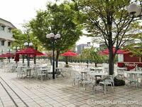 宝塚大劇場での飲食について。現在、6/20まで大劇場内のレストランや、改札内での飲食は中止となっていますが、改札を出たところにある写真の屋外スペース(武庫川沿いに設けられているテラスのような場所です)での 幕間の飲食は可能なのでしょうか? 例えば観劇前に弁当を購入して、幕間にこちらのスペースで食べる、などは可能ですか?ご存知の方、教えてください。