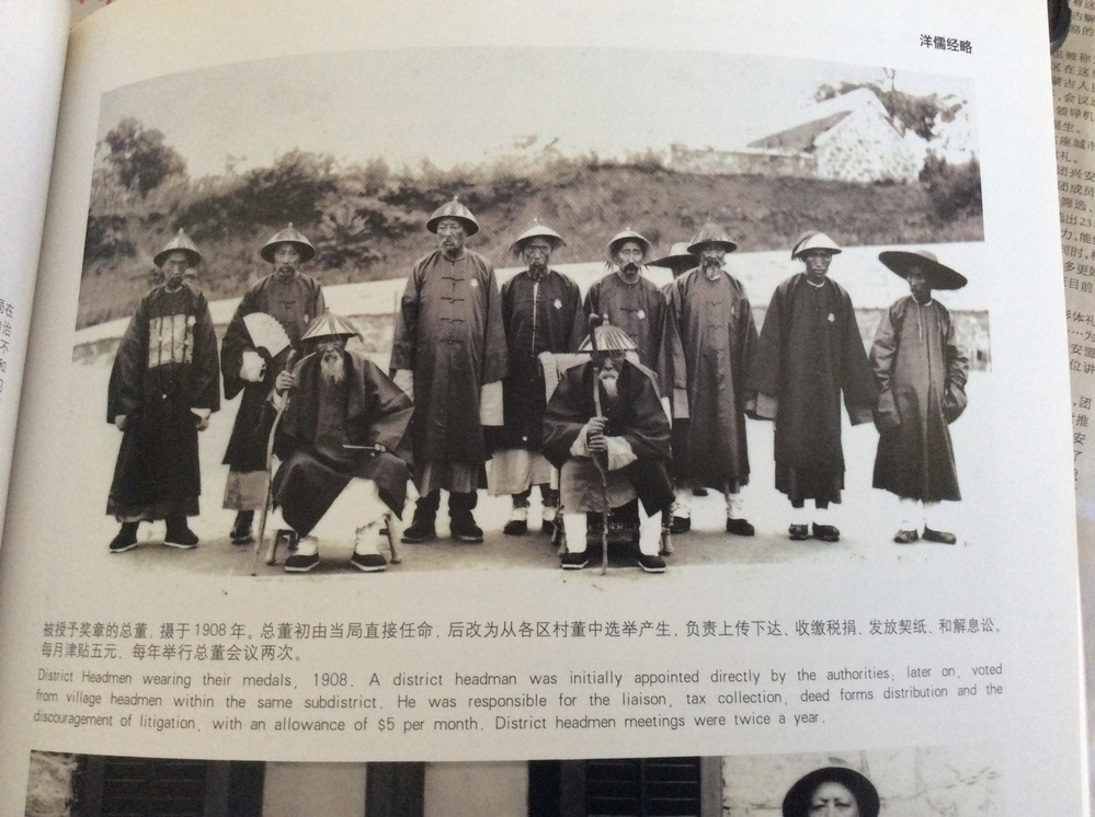 District Headmen wearing their medals, 1907. A district headman was initially appointed directly by the authorities; later on, voted from village headmen within the same subdistrict. He was responsible for the liaison, tax collection, deed Fromm distribution and the discouragement of litigation, with an allowance of $5 per month . District headmen meetings were twice a year. この文章を日本語で翻訳して欲しいです、宜しくお願いします。