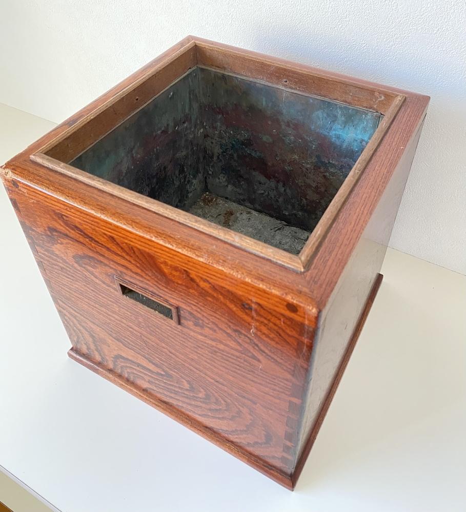 質問お願いします。 倉庫から出てきました。木製で、サイズは25cm四方です。内側には薄い金属板が貼ってあります。 明治時代の本や、小箱などと一緒に入っており、かなり昔のものと思います。 小さな火鉢や灰皿でしょうか? どなたかお詳しい方、教えて頂けると助かります。 よろしくお願いいたします。