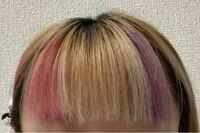 セルフカラーの失敗について。 先程セルフで前髪の一部をメッシュ風にカラーをしました。  ピンクと紫のヘアマニキュアで染めたのですが、自分的には納得できず…  なんとかこの部分を修正する方法はありませんか、?  正直この部分を切ってしまいたいほどです…(T . T)  前髪を増やして隠すとかは既に前髪厚いので不可能ですかね…