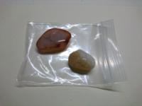 天然石屋のガシャポン(100円)で出たものなのですが、それぞれなんの石か教えてください。 左→乳白色に、ケチャップのような色の模様 右→乳白色+琥珀色。内部で細かくひび割れていて、光を当てるとキラキラする