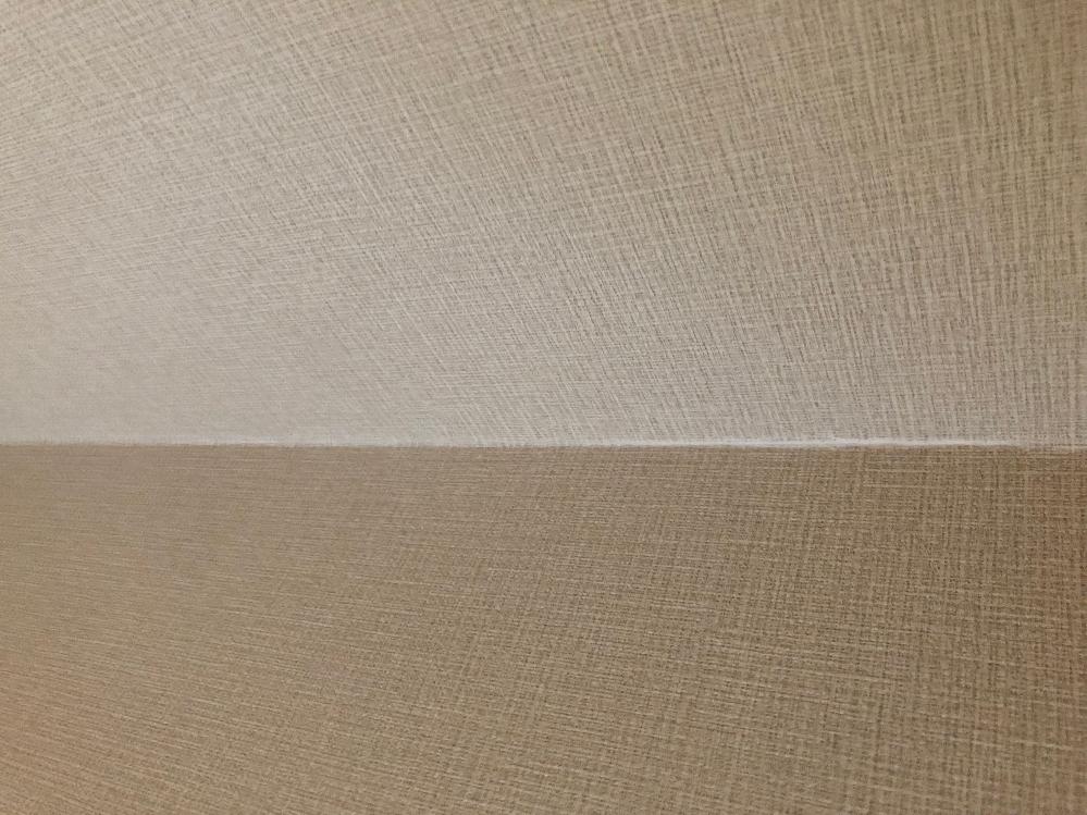 家のリフォームについて質問です。 中古マンションを購入し現在壁紙とフロアの一部をリフォーム中なんですが、至る箇所で仕上がりが雑でとても不安に感じています。 今回の質問は、貼り替えたばかりの壁(部屋の角部分)に一部破れがありました。数日前に張り替えたばかりで角部分と言えど破れたりするものでしょうか? またその箇所の修正をお願いすると、添付写真のようにボンド? 目地材で補修してあるのみでした。 何年か後に剥がれや破れなどがあった場合にその様な対応もわかる気がしますが、壁紙の張り替えをしたばかりでいきなりこのようにボンドのようなものを塗るものでしょうか? 素人なので作業工程などわからない事ばかりですが、色々と雑な感じがして不安です。 どなたかお詳しい方がいらっしゃれば、教えていただきたいです。よろしくお願いします。