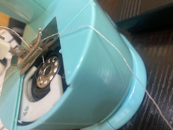 ミシンの下糸はどのように通せばいいんですか?? この写真で分かりますか? 手前にきてるのが下糸です。