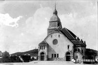 """青岛基督教堂由胶澳德国总督出资,始建于1908年4月19日,由密斯特公司施工,1910年10月23日竣工。 1907年6月1日,德国柏林教会(信义会)通过远东的各大西方报纸刊登启示,向东亚的西方建筑师征集青岛基督教堂的设计方案。罗克格参与竞标并最终获得了成功。1909年3月26日柏林出版的《德国建筑业报》,曾经刊登过罗克格的一篇文章,阐述了这座基督教堂的创作思路:""""鉴于各种设施均设在建筑底层..."""