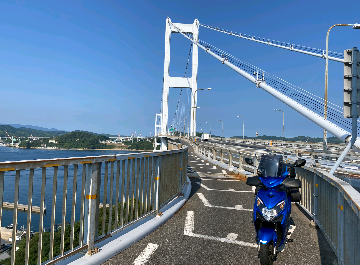 スズキの原付スウィッシュリミテッドは、日本で手に入る125ccスクーターとしては、S,A,B,C,D,E,Fでランク付けするとどのくらいのレベルになりますか? 現在ボロボロのPCXの初期型jf28に乗っています。91,000kmを越えてさすがに色々と限界がきてしまっていて乗り換えを検討しているのです。じつはその昔に乗っていたアドレスV125Gが非常に頼もしく、加速は速い、長持ちした、たまの長距離も気軽に乗れた、すごくで良かった思い出がありまして、久しぶりにスズキの原付に戻っても良いかな? と思っているのですが、ろくなラインナップがありません。 スズキのフラッグシップ原付としてこのバイクがあることを知り、バイク屋さんに伺ったところ、なんと生産終了で在庫限りなので決めるなら早めに!という通告を受けてしまいビックリしてしまいました。 値段的にはPCXの新型という手もあるにはあるのですが、乗り飽きている部分もあって迷いもあります。乗り心地は最高に良かったのですが、現行は装備の豪華さもありますが、乗り心地もかなり進化しているのでしょう。正直、これでスウィッシュにしてしまったら格落ちになりますよね?w バイク屋さんからもそれなりに話はいただいてきましたが、一般のみなさんからのスウィッシュリミテッドという車種はどういう評価になりますか? バイク屋さんは戦闘力はぜんぜん低くない、というお話でした。 私はヒーター完備とまだ昔のアドレスを引いている風の見た目が気に入っています。普段は往復26kmの通勤ですが、たまの休みには海へ山へ行きたい...そんな思いです。写真は拾い画なのですが大きな橋みたいなところも小柄だから通れるのかな?と思っています。 改めて、みなさんからの車体のランク付けと、プラス、マイナス含めて幅広い意見を参考にしたいのでよろしくお願いします!!
