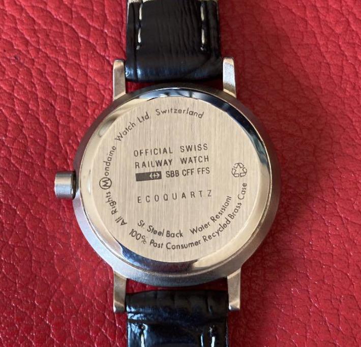 """モンディーンというスイス国鉄オフィシャル腕時計に、竜頭がリサイクルを示すロゴでデザインされたモデルがあるようですが、どういう取り組みで生産されたものでしょうか。 裏蓋には通常のモデルには無い""""100% Post Consumer Recycled Brass Case""""という文言、リサイクルのロゴが刻まれているようです。"""