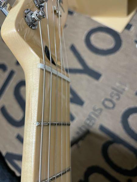 エレキギターを新品で購入したのですが6弦が開放でビビります。 そこでナットの写真を撮ったのでナットに異常はないか判断して頂けないでしょうか? 5弦より6弦の方が盛り下がってるのですがこれは異常ですか?