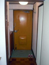 うちの玄関です。現在はなにも飾ってません。アドバイスを! 借家 古いアパートです。 黄色の鉄のドア、つくりつけの合板ベニヤ製の靴箱。 緑のコンクリートのたたきです。 向かって左はトイレ、右は洗面です...