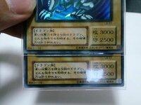 どちらかの青眼の白龍は偽物ですか?青眼の白龍LB-01を2枚持っているのですが、重ねている下のカードは上のカードに比べるとテキストが太く、また「青眼の白龍」というカード名が少し左に寄っています。 こ...