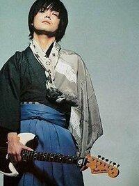 この写真に映っている人は誰ですか?  着物を着て、エレキギターを持っている男性です。  わかる方がいらっしゃるのなら、ご回答お願いします。 写真を見てお分かりになられるでしょうが、一応文章でも書いて...