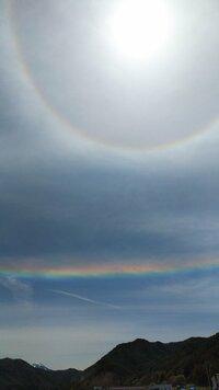 彩雲が出ていますが、いままで 見た事ないくらい、彩雲がキレイです。 天変地異の前触れでしょうか? 10時頃の太陽の周りの彩雲は 太陽の周りに円を描いて出てましたが、 12時頃のは太陽の下に水平に出ています。  写真は12時頃の彩雲です。