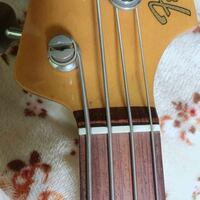 ジャズベース 4弦について 1~3弦のように、ストリングポストからナットに向けて弦が真っ直ぐ降りてくるのが普通だと思うのですが、このベースの4弦はナットに向けて若干曲がっています。これは何かを間違えて弦を...