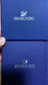 スワロフスキーについて質問です。 上の画像の箱は、自分でスワロフスキー 正規店で購入した時に入っていた箱です。  下の画像の箱は、プレゼントで頂いた時に入っていた箱なんですが、スワンも違うしスワロのロ...