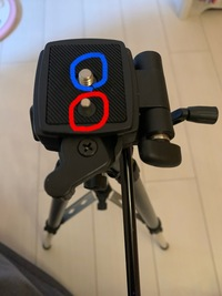 三脚の使い方について質問です  初心的な事だと思いますが カメラに詳しい知り合いが居ないので よろしくお願いします  写真を載せました。 青い丸印は一眼レフを止めるネジですよね。  もう一つ 赤い丸で囲ったところは は指で押すとへこみます。  この赤い丸で囲った出っ張りは 何のためについてるのですか?  一眼レフをネジにつける時 一眼レフをぐるぐる回してつける...
