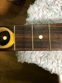 エレキギターの弦交換するついでに指板にマスキングをして、フレットを鏡面コンパウンドで磨いてたら何か取れて色が抜けました。マスキングテープの粘着力で取れたみたいです。 作業時間は10分ほどでした。  表面...