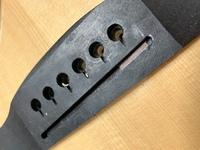 アコースティックギターの弦高調節をしようと思って、サドルを外してみたんですけど、 サドルの溝に何か木材が挟まっているんですけど、これってなにかわかりますか?? また、削るんだったら溝とサドルどっちを削ったらいいですか??