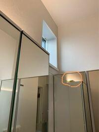 光源を隠すには 洗面所に、三面鏡の鏡をL字に並べて設置しました。  写真の三面鏡の上に、コイズミ照明さんの棚の上などに設置できる照明を置いたのですが、合わせ鏡になって少し光源と配線が見えてしまいます。  鏡も照明も、どちらも90cmの長さなので、照明はこれ以上ずらすことができません。  トイレにも幅90cmの三面鏡に同じ種類の照明を設置したのですが、照明は60cmの商品を設置したので配線は見...