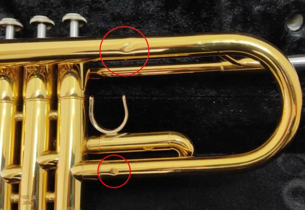この楽器の凹み、修理代はいくら? ・ トランペットに凹みがあります。赤丸の部分の凹みを直すには、いくらくらいかかるでしょうか? 概算でけっこうです。また、これは半田付けを取り外してからでないと修理できないでしょうか? よろしくお願いします。