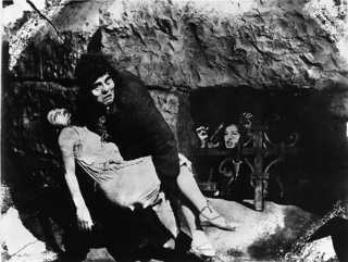 【てんぷら☆映画復活祭】Scene#378 皆さん、映画はお好きですか? ではこのワンシーンで ひとつ 素敵なボケをいただけますか? (・▽・) 『ノートルダムのせむし男』より ☞15世紀、ルイ11世治下のパリ・・・ノートルダム寺院では容貌怪異のカジモドという傴僂(せむし)男が、鐘つきをつとめていた。 年一回の道化祭、詩人グランゴアールは、広場にやって来た美しいジプシー娘エスメラルダに人気をさらわれ、自分の芝居をメチャメチャにされてしまう。 一方ノートルダムの副僧正フロロも、美しいジプシー娘に、忘れていた煩悩の火をかきたてられ、忠実なカジモドに命じて、その夜エスメラルダを誘拐させた。 しかし彼女の叫びに駈けつけた警備隊にカジモドは捕えられ、エスメラルダの方は隊長フェビュスを恋するようになった・・・