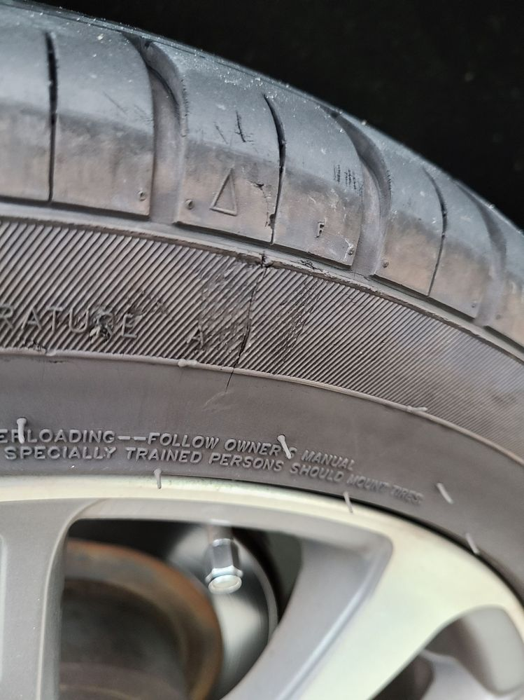 車タイヤのパンクのイタズラ判定 Y50フーガ(セダン)に乗っているのですが、 車の調子が悪くディーラーに行きました。 全く気付いていなかったのですが、 左後ろタイヤに空気が入ってないと指摘されました。 いつから抜けていたのかも不明です。 走行に全く違和感を感じなかったので。 空気を入れてみると240kPaが正常なのに、 50kPaしか入ってませんでした。 空気を入れた後に気付いたのですが、 画像の通り、側面に傷がありました。 画像には写ってないですが、 同じような傷がもう1か所ありした。 ディーラー店員が霧吹きで、 傷からの空気漏れチェックをしてくれました。 でも、漏れている様子も無く、 様子見と言うことで帰宅となりました。 ディーラー店員の意見としては 空気が少ない状態で縁石に擦ったのでは? との事でしたが、擦ったような感じ無いですよね。 走っている時に徐々に漏れているのですかね? 一番聞きたいのはこれはイタズラかどうかです。 判定を宜しくお願いします。 ちなみに恨まれる覚えは無いのですが。