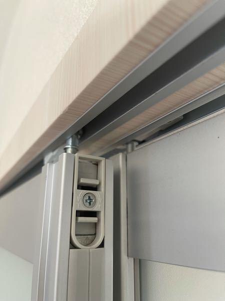 室内吊り下げガラス引き戸の吊り下げ部品が外れません。 レール側のタイヤ部品と戸側の吊り下げ部品が外れてしまったため、構造上、写真の部分を外してレールに嵌めてから 扉を付け直さないとないとならないのですが、 外し方がわかりません。 中央のネジは、高さを調整するためのものらしく、どっちにギリギリまで回しても部品自体はグラつきさえしません。 どなたかこの部品の外し方をご存知でしたら、教えてください。 メーカーもわかりません(もしわかれば教えてください)。 よろしくお願いいたします。