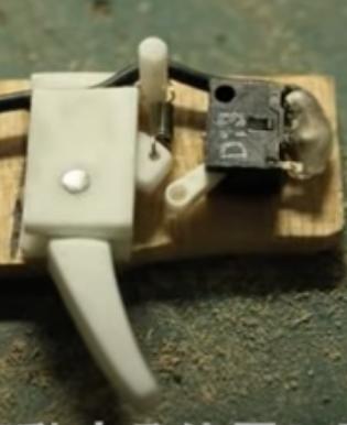https://www.youtube.com/watch?v=ukAq0ym6lw0 この立体機動装置を再現しようとしています。白いレバーを引くと回路が作動して糸を巻き取るかとが出来ます。この回路を作動させられる黒い物をなんて言うのか教えてください。