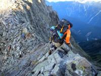 西穂高岳から奥穂高岳の稜線は、 ジャンダルムや馬の背などの 難所を越えます。  足元や手掛かりは、 しっかりしていますが、 ハシゴや鎖でなく、岩を頼りに、 身体を支えます。  何時間もかかるので、 身体が疲れるだけでなく、 緊張が持続しません。  気をゆるめると、 滑落して死にますので、 ここらで一服したいと、 何度も思ながら、 ゆっくりと休める場所も心の余裕も、 ない。  断崖絶壁にへばり...