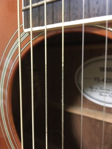 ギターについての質問です。 エリクサーの弦を使っているのですが、ピッキングをする部分が下の写真のように、コーティングが剥がれたようになっています。3弦、4弦が特にです。この弦は3週間ほど使っていてまだ1ヶ月も使っていません。ほかのエリクサー使っている人はもっと長持ちしている印象です。 もうこの状態になったら、もう弦を変えた方がいいですか? また、この状態になったのはなぜなんでしょうか。