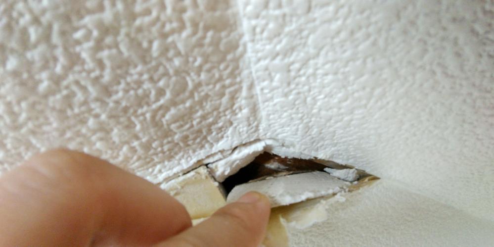 築30年リフォーム済みの物件を購入しました。 屋根裏部屋の壁紙が所々浮きがある所があったので めくってみると写真の様な状態でした。 この白い物は何でしょうか? 触るとボロボロと崩れます。