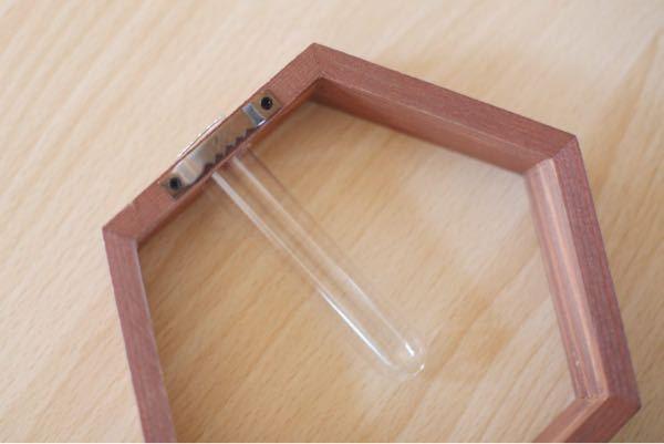ダイソーで六角形の【壁掛け一輪挿し】を買ったんですが、壁にどう掛ければいいのかわかりません…(´・ω・`;) 裏が画像のようになってるのですが、引っ掛けられるような細めの画鋲やフックピンも見つかりませんでした。 紐を通して吊るすしかないですか? どなたか教えてください!よろしくお願いします><
