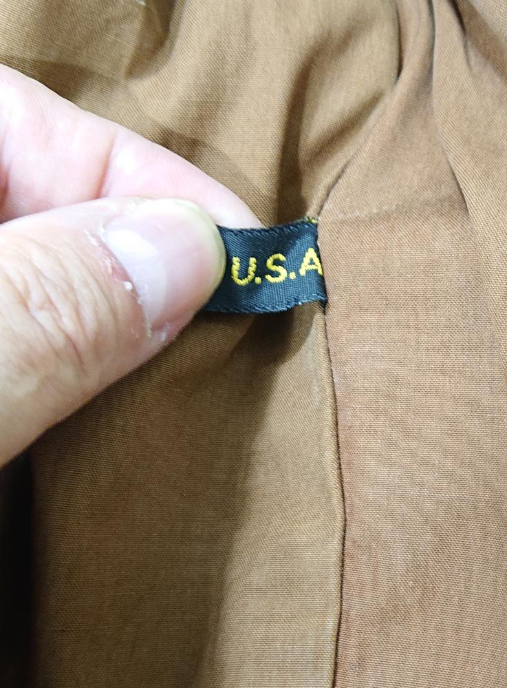 A-2フライトジャケットについて。 実モノであろう1着を譲って頂けるとの事で実物を見ました。 タロンジップから60'sだと予測は着きそうですが、気になる点があり博識の方に教えて頂きたいです。 インナーに画像の様なMADE IN USAのタグが右脇腹あたりに着いていました。そのタグだけやたら綺麗で何処かのレプリカ?か?と思いました。当時この様な生産国タグを軍支給品についていたのでしょうか? ミルスペックは劣化でほとんど読めませんでした。生産メーカーも読み取ることが出来ません。 どうかお力をお貸しください!
