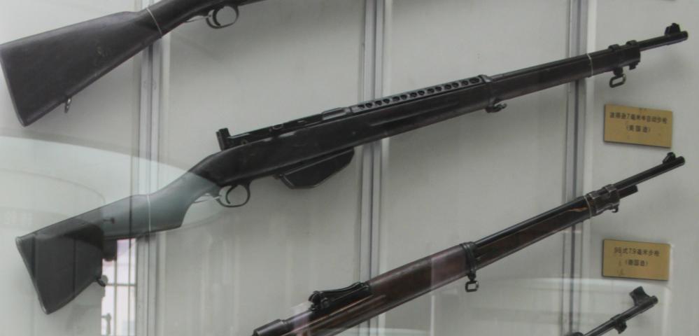 この画像の銃を教えてください ピダーセン自動小銃の画像ですが ピダーセン自動小銃の下にある銃はなんの名前の銃ですか? 一応名前が書かれていますが中国語で書かれていまして しかもぼやけています もし知っている方お願いします 画像は中国人民革命軍事博物館の画像です